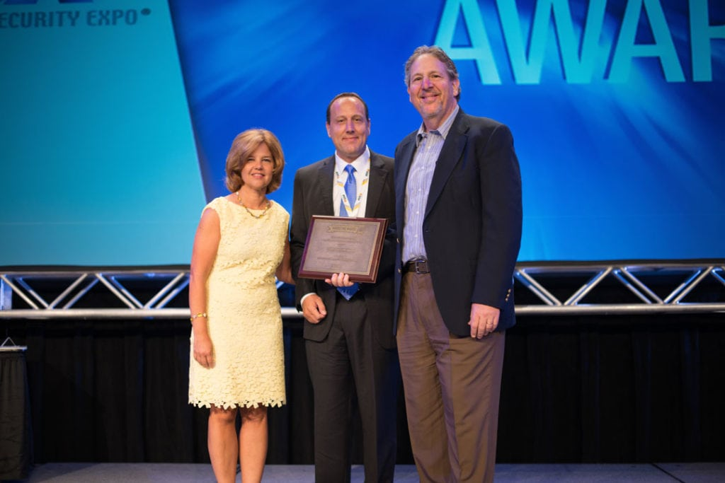 CSAA's Pam Petrow (left) and SSI's Scott Goldfine (right) give 2015's Marvel Award to COPS' David Smith